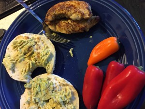 Bagel smeared with avocado, chicken breast tenders, mini peppers